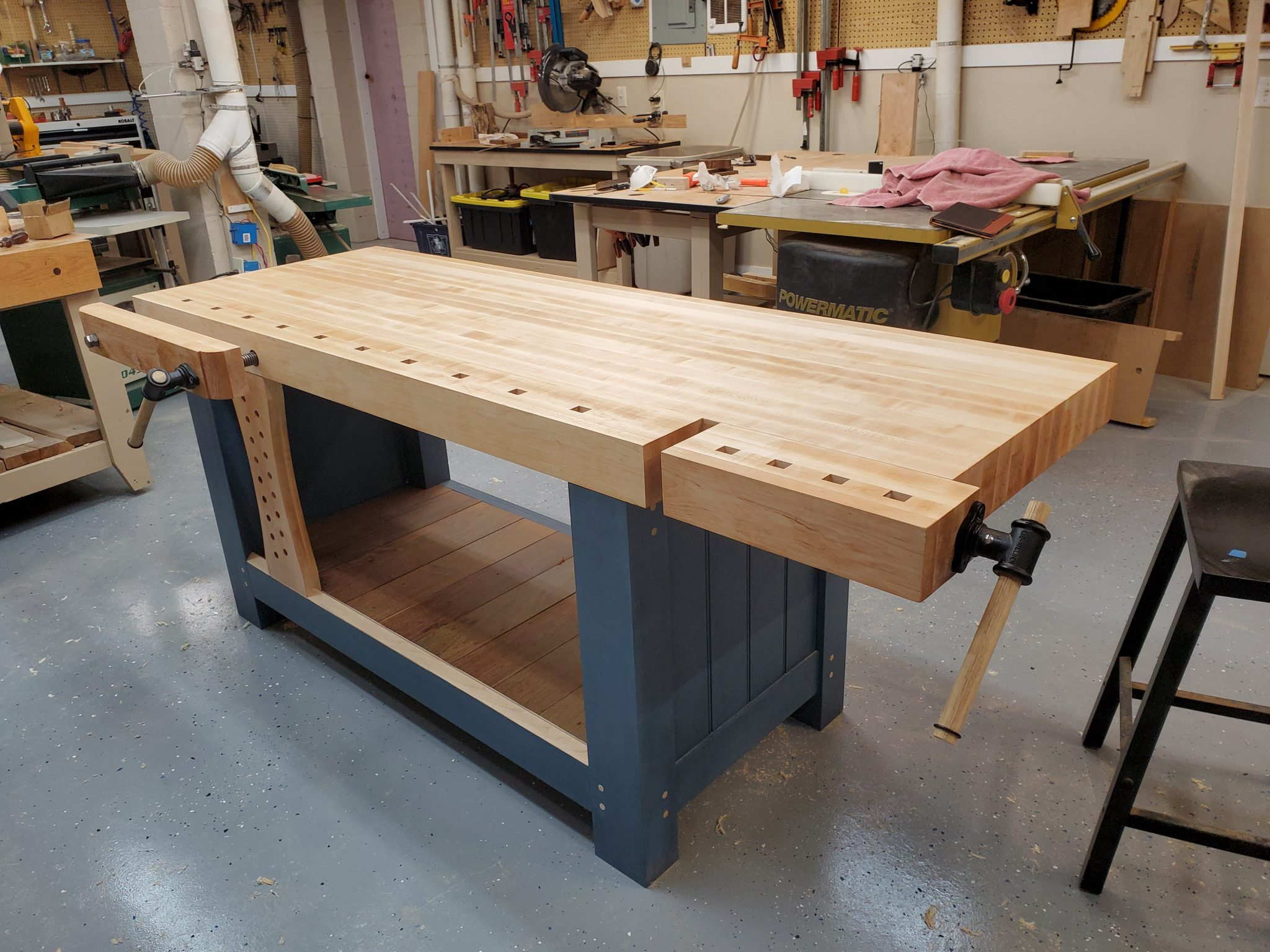Shaker inspired work bench with end and twin screw vise.  Maple with milk painted base