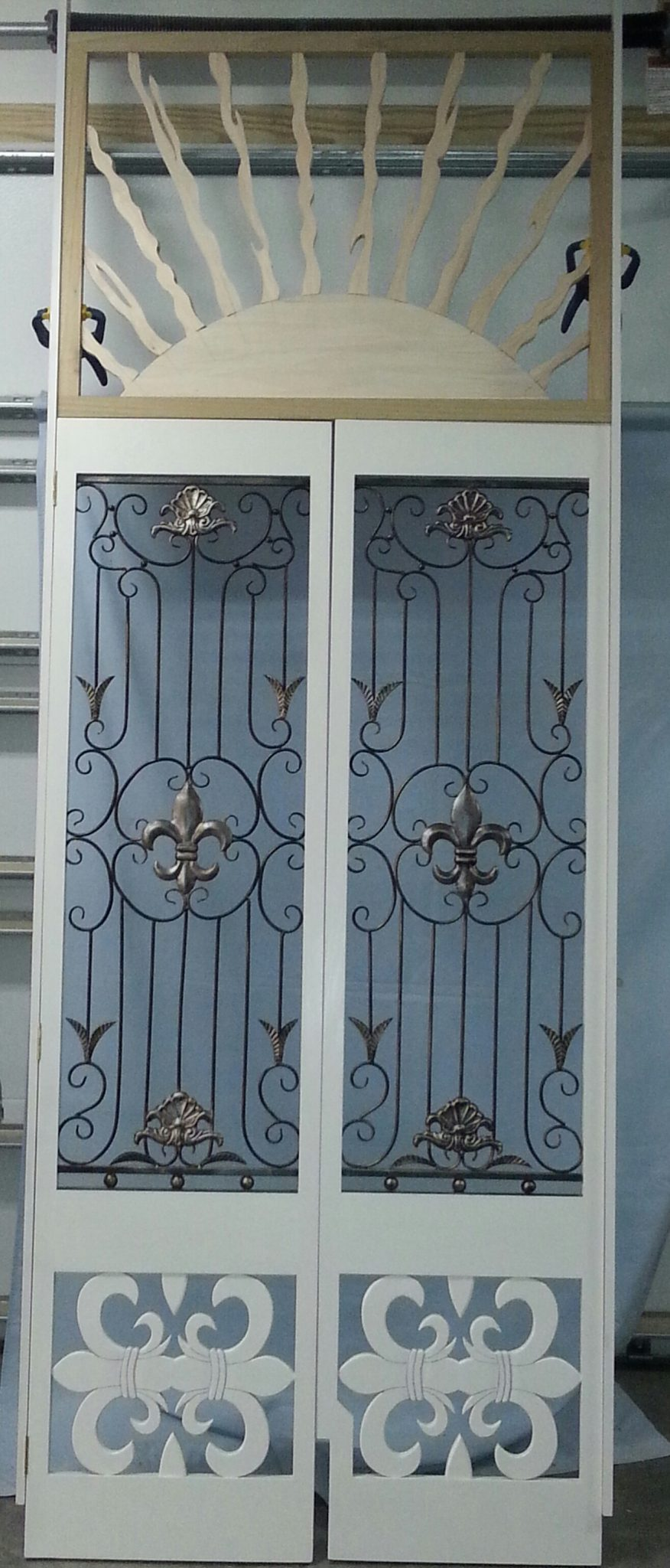 Custom made door set for a stairway entrance, using the customers metal flour delis grilles.  The top sunburst is also painted white.
