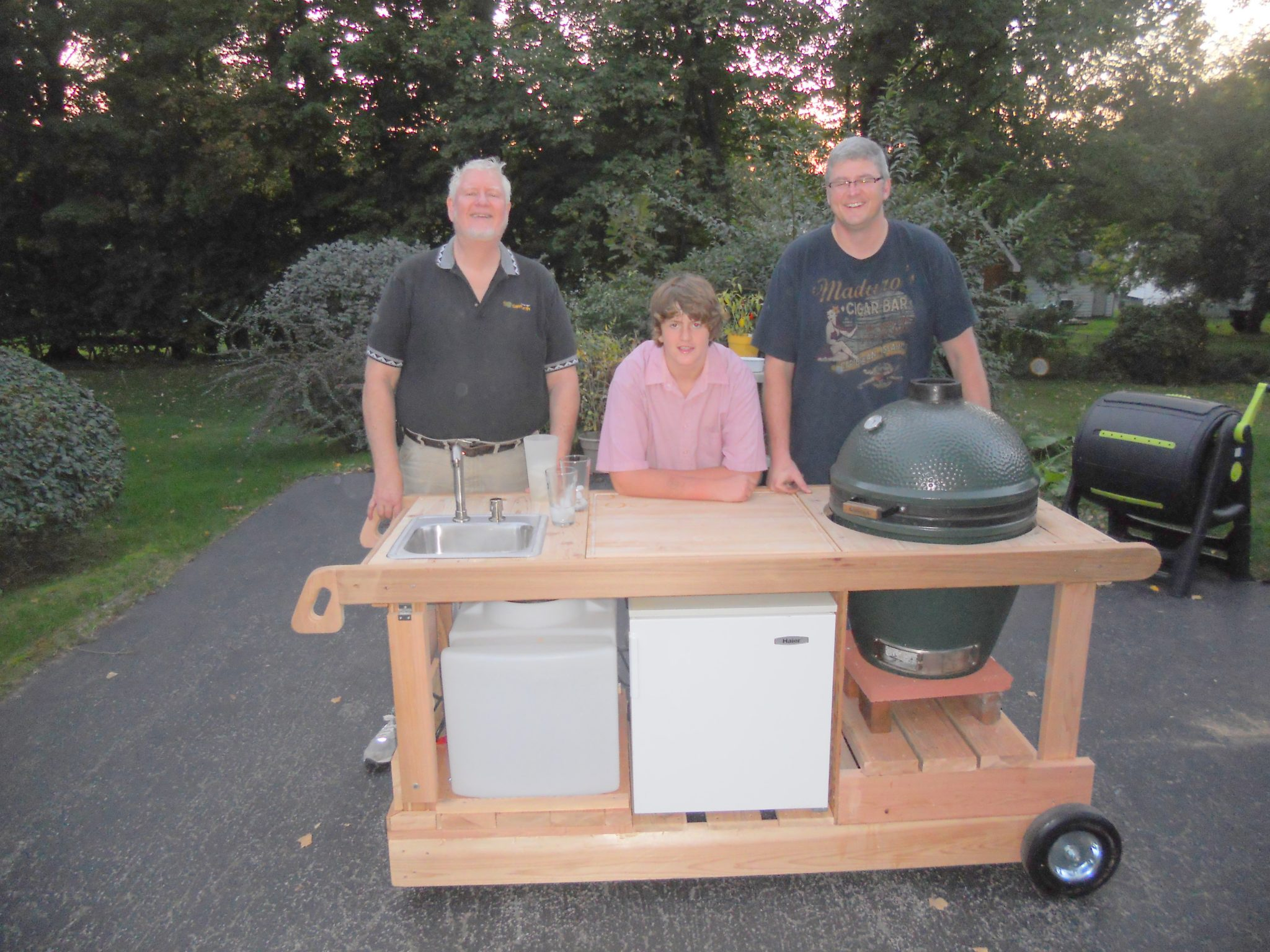 BBQ Cart with sink, Water tank, Refrig, Big Green Egg Cooker, & cutting board.  Built for My Middle son. Shown with Grandson.  Made from Cedar.